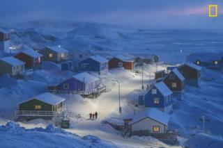 An snow-covered view of a street in the fishing village Upernavik in Greenland