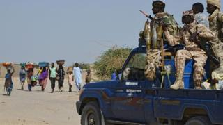 People from the Nigerian town of Malam Fatori an its area, close to the borders with Niger and Chad, pass by a car with Chadian Gendarmes (in uniform) as they flee Islamist Boko Haram attacks to take shelter in the Niger's town of Bosso secure by Niger and Chad armies, on May 25, 2015.